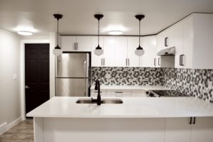 basement rental suite white kitchen ikea quartz island peninsula pendant lights glass hex tile backsplash