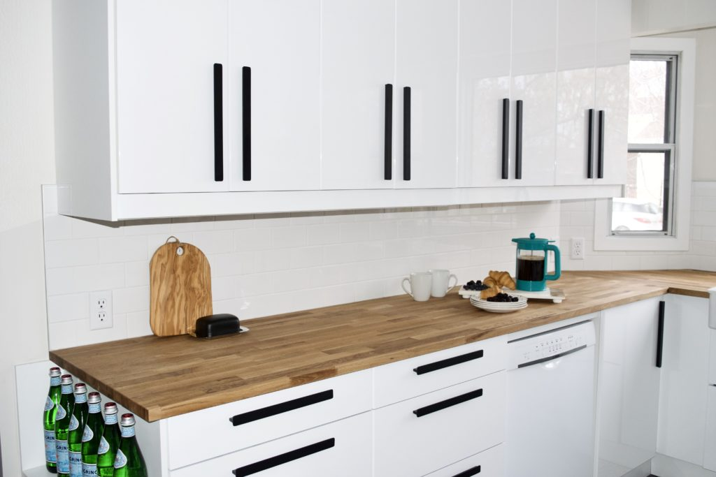 black and white modern farmhouse kitchen black handles white gloss cabinets butcher block counters white subway tile ikea hackas ringhult