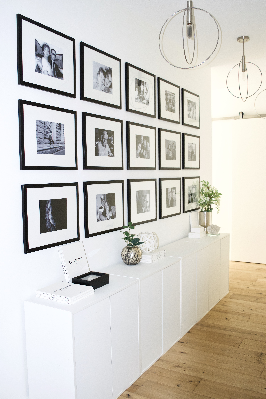 hallway entry gallery wall floor to ceiling white cabinets black frames glam scandinavian ikea oak wood floors white walls