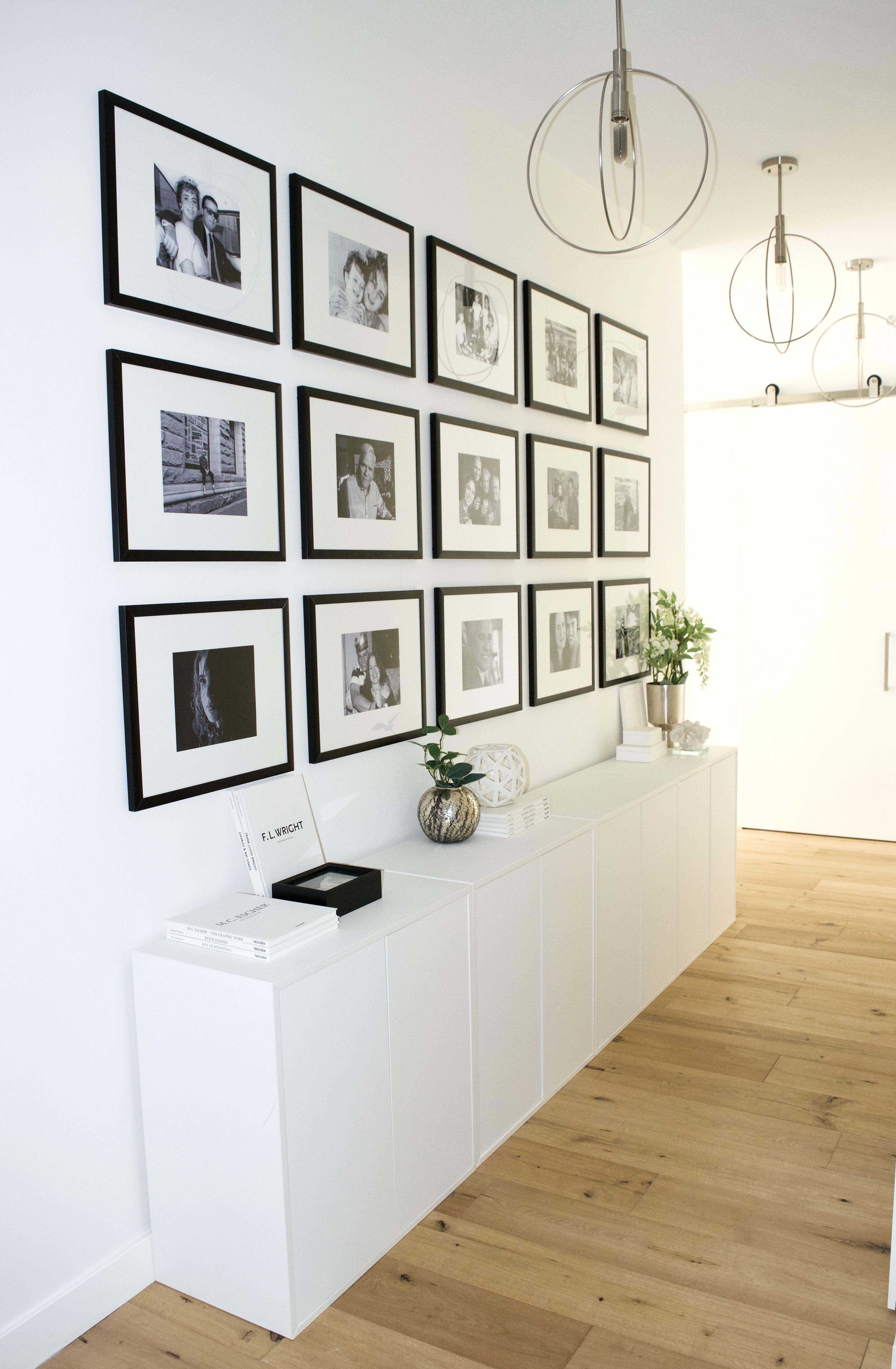 hallway entry gallery wall floor to ceiling white cabinets black frames glam scandinavian ikea oak wood floors white walls