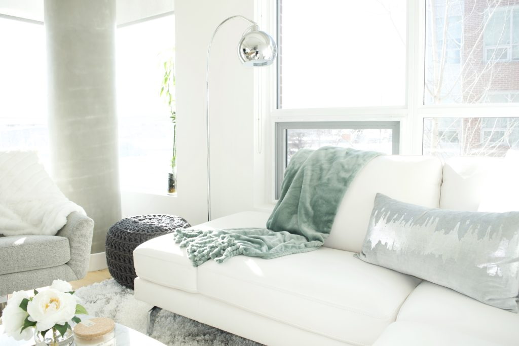 modern scandinavian scandi glam white grey black ivory concrete pillar design swivel chair sectional silver decor living room apartment small space marble table white leather sectional seafoam green pastel soft bright white paint calgary interior designer home by freya maclean pouf ottoman knit arc lamp leather couch corner pillows tassel blanket
