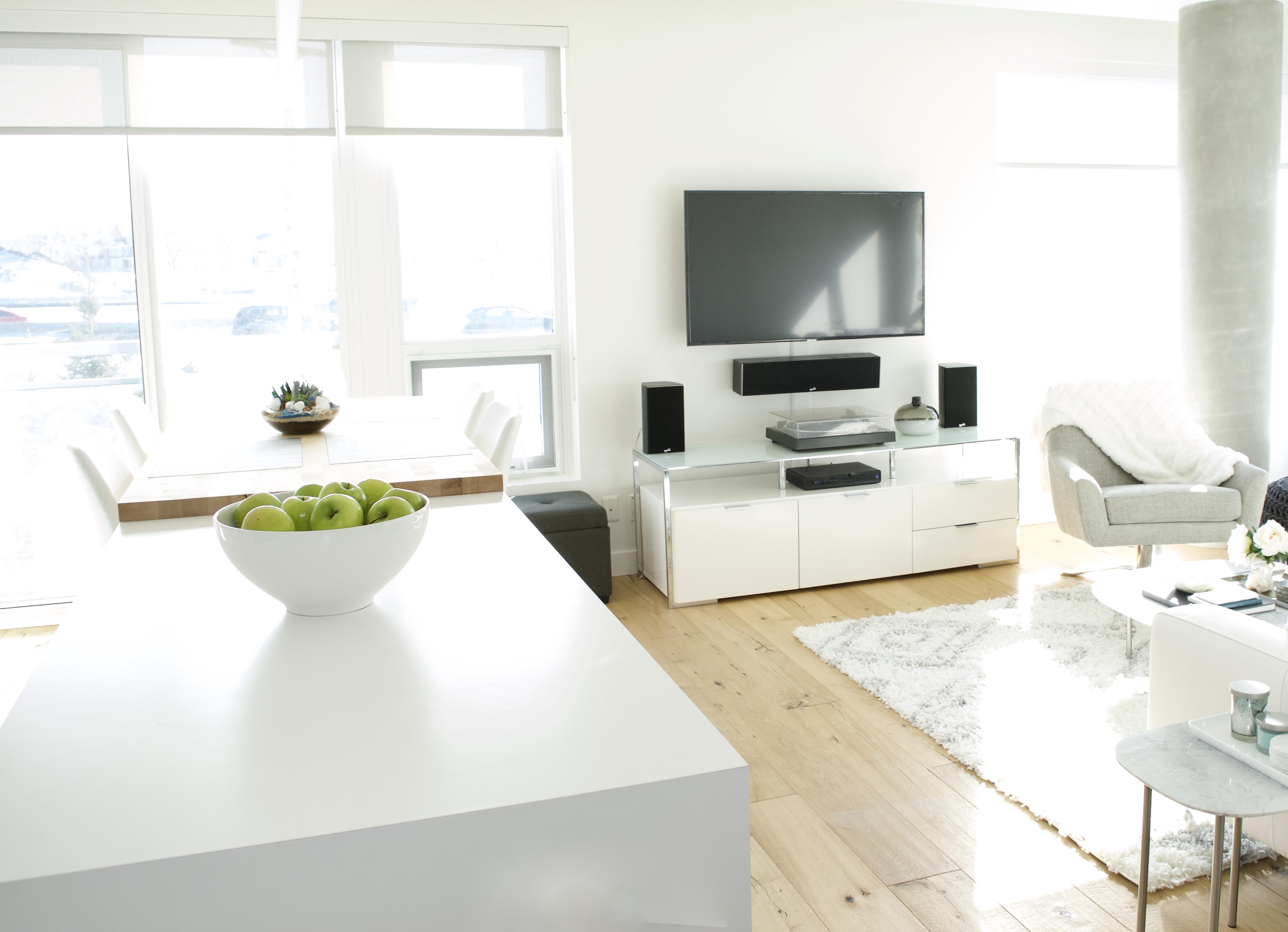 open concept living room kitchen modern apartment calgary inner city interior design tv oak floors white black grey windows high ceilings