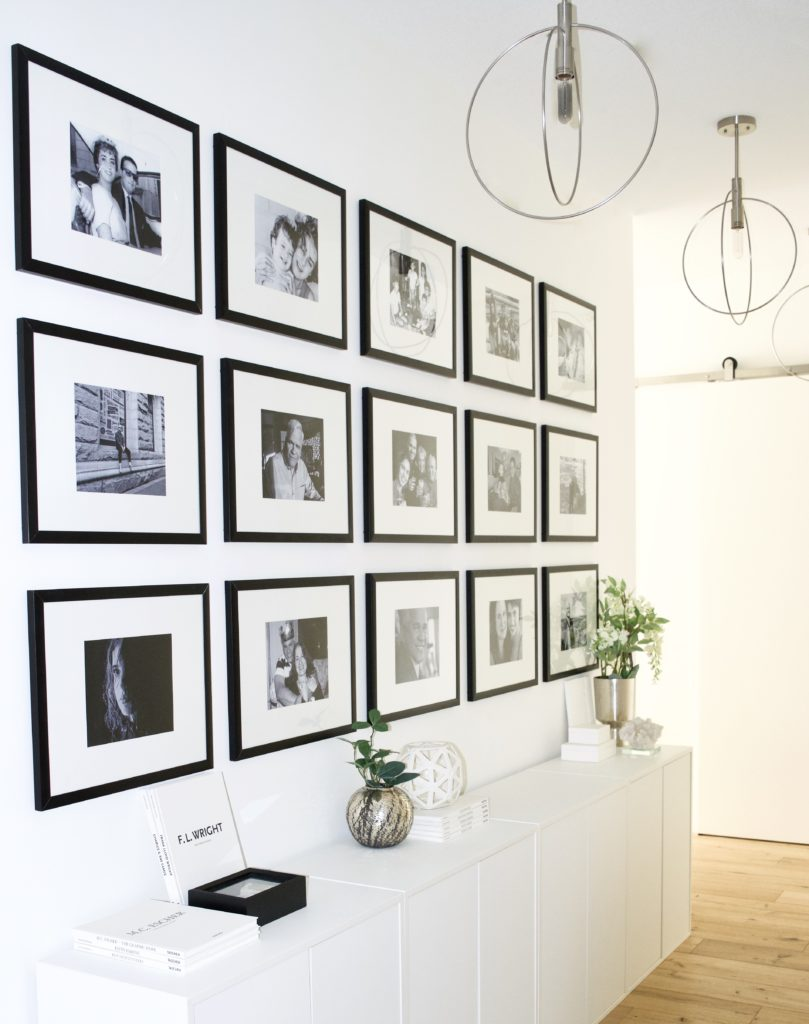 hallway entry gallery wall floor to ceiling white cabinets black frames glam scandinavian ikea oak wood floors white walls grid